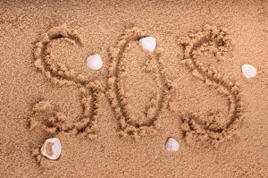 """Drawing of """"SOS"""" on the beach sand at the sea."""